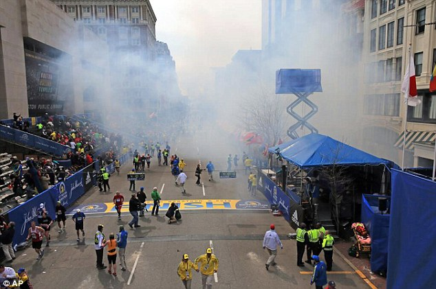 Moments after: Smoke billows from near the finish line after the bomb was detonated, inflicting tragedy