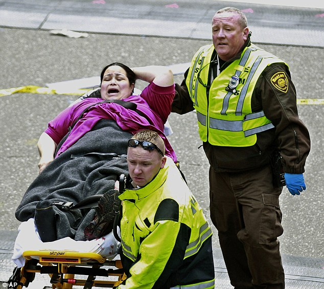 Screams: Medical workers aid an injured woman. Scores are believed to have been hurt, and two killed