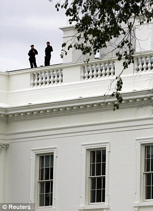 U.S. Secret Service agents stand on top of the White House amid the heightened security around the area