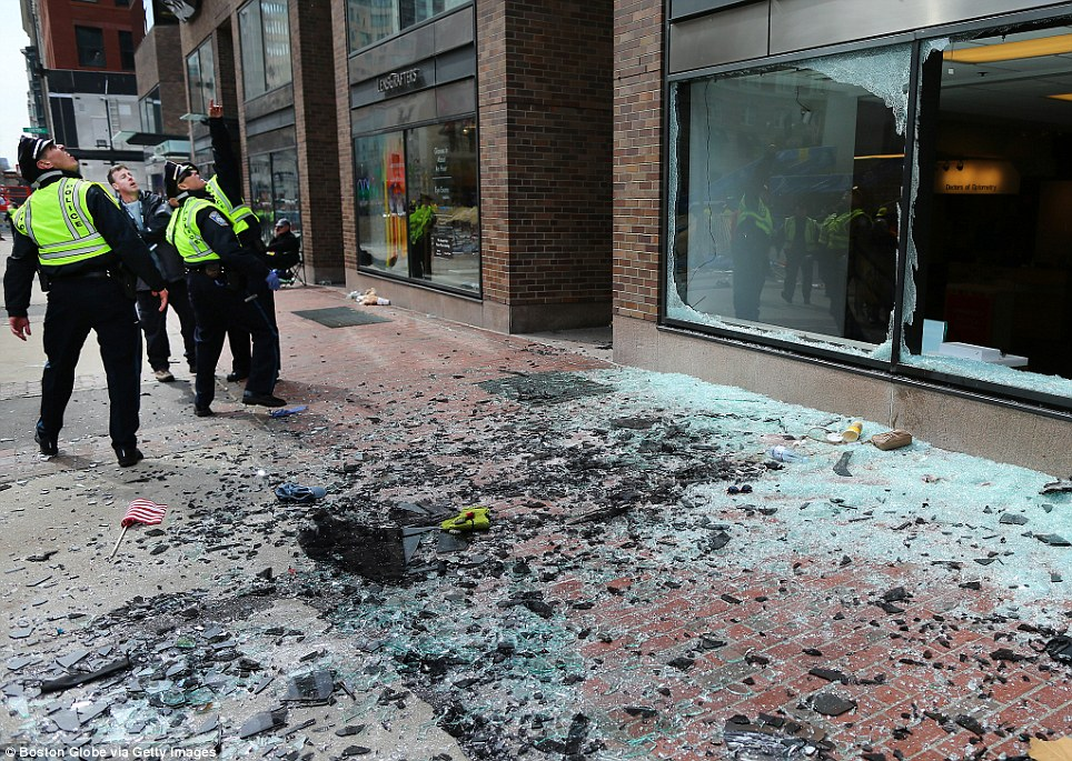 Boston police examine the damage following the massive twin detonations today at the Boston marathon