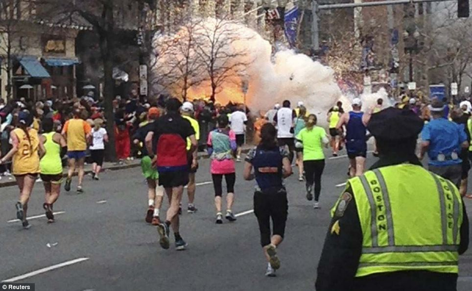 Blast: Runners continue to run towards the finish line of the Boston Marathon as an explosion erupts near the finish line of the race