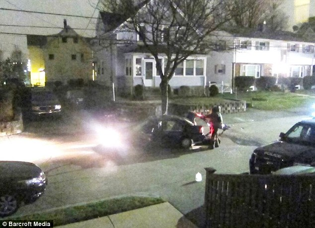 After the shootout: Investigators take a look at a car driven by the Boston Marathon bombing suspects after they exchanged gunfire on a residential street in Watertown