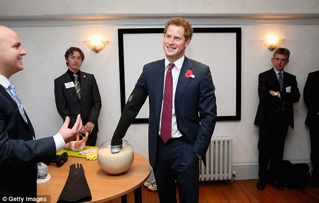 Prince Harry wears a glove to experience what it is like to have a brain injury