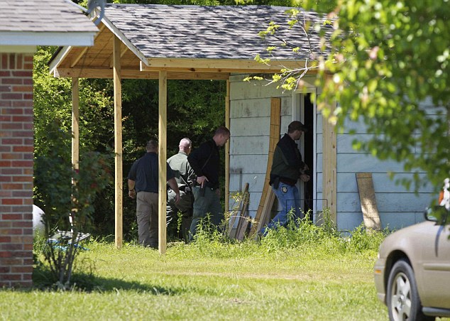Search: Officers search the grounds of the home of Melvin Kitchens as they try and help federal authorities locate Everett Dutschke near the town of Kirkville, Mississippi on Thursday