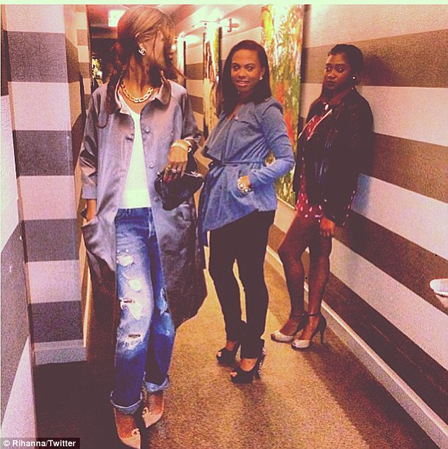 Eating out: Rihanna posted another snap of herself in casual jeans and trench coat with two girlfriends and the caption: 'Off to dinner with my side orders'