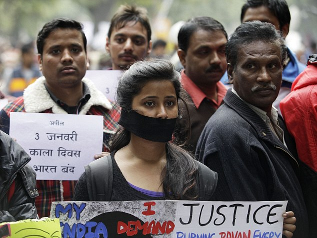 Indian protesters hold banners and wear black ribbons during a rally in New Delhi in December