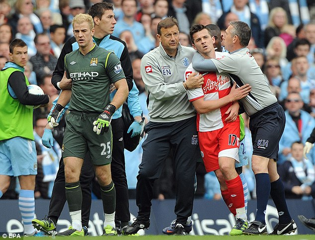 Last-day disgrace: Joey Barton has to be escorted from the pitch following his sending off at Manchester City on the final day of last season