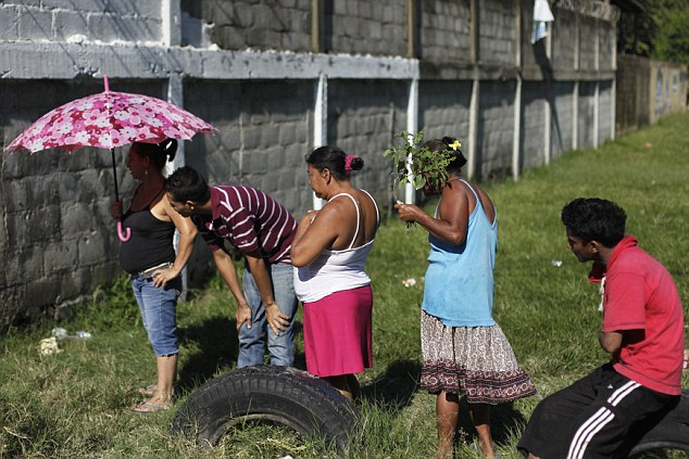 Common sight: People stand near a crime scene where a man was shot dead by gang members. More than 80% of homicides are by firearms, compared to 60% in the United States