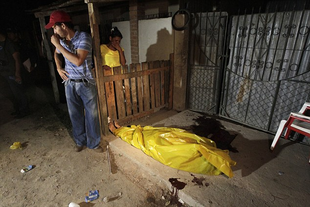 Too much to bear: Family members break down while standing next to the body of a woman who was shot dead by two gunmen on a motorcycle in San Pedro Sula last month