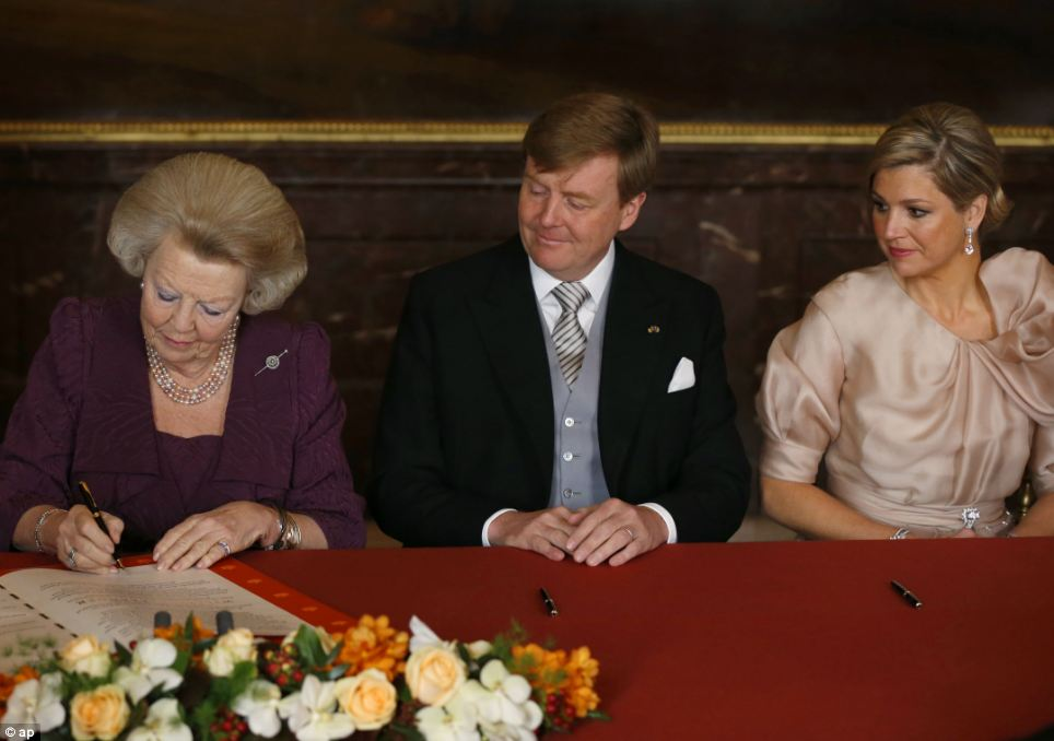 End of an era: Queen Beatrix of the Netherlands signs the act of abdication next to her son Crown Prince Willem-Alexander and his wife Crown Princess Maxima during a ceremony at the Royal Palace in Amsterdam