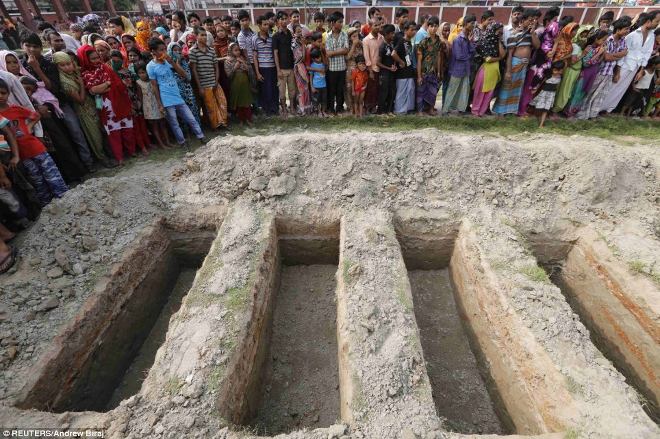 A country in mourning: A crowd gathered in front of the row of graves at the traditional Muslim funeral today, following the horrific collapse that exposed the unsafe conditions plaguing Bangladesh's garment industry