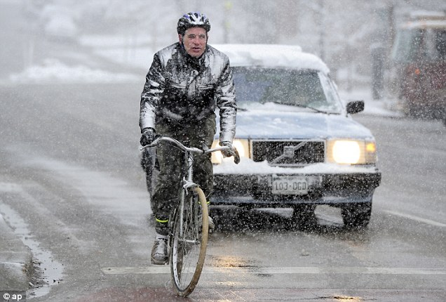 Icey: Dan Hopkins, rides his way to work as the snowstorm passed through Boulder, Coloradok during the Wednesday morning snow in Boulder, Colorado