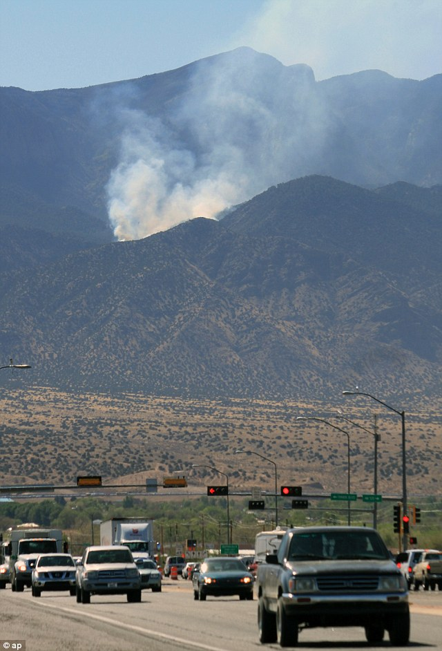 Smoke spreading: Traffic passes on U.S. 550 as smoke billows from a wildfire burning in the Sandia Mountains near Bernalillo, New Mexico