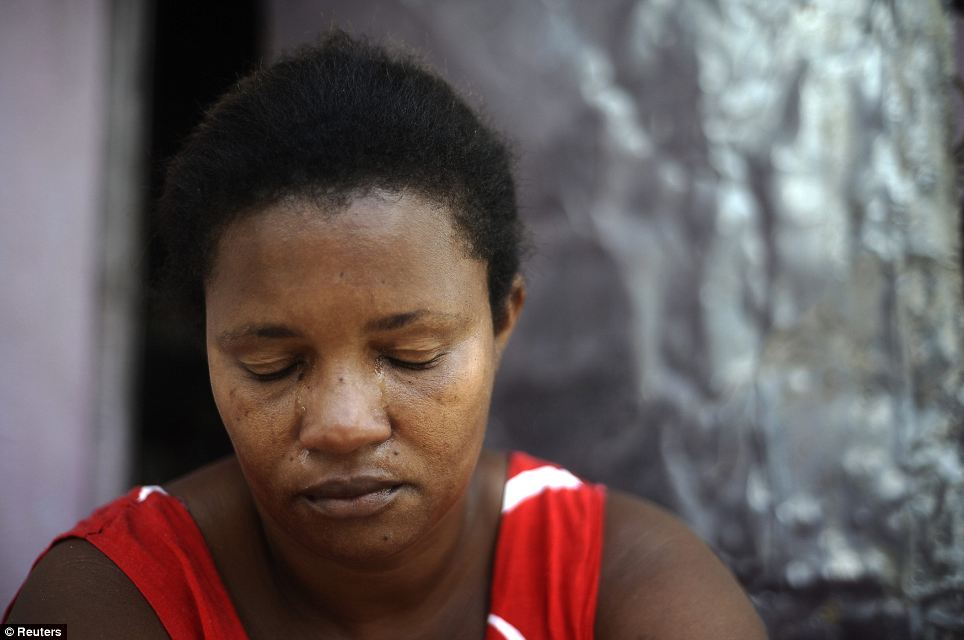 So many tears: Ana Claudia, who witnessed her son Reinaldo being beaten and shot dead by drug traffickers, cries during an interview in the Fazendo Couto slum