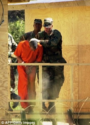 High security: Soldiers take a prisoner for questioning at Guantanamop in 2002