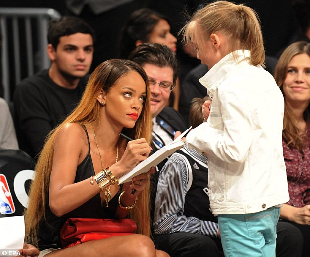 Kind gesture: Rihanna signed an autograph for one thrilled young fan