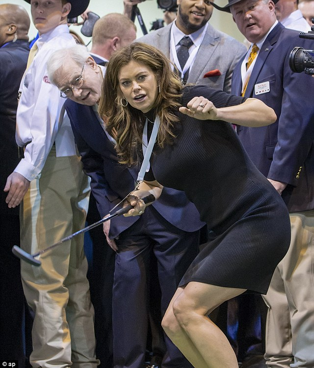Still got it: Former super model and now business woman Kathy Ireland and Berkshire Hathaway Chairman and CEO Warren Buffett follow Ireland's golf putting prior to the Berkshire Hathaway shareholders meeting in Omaha, Nebraska