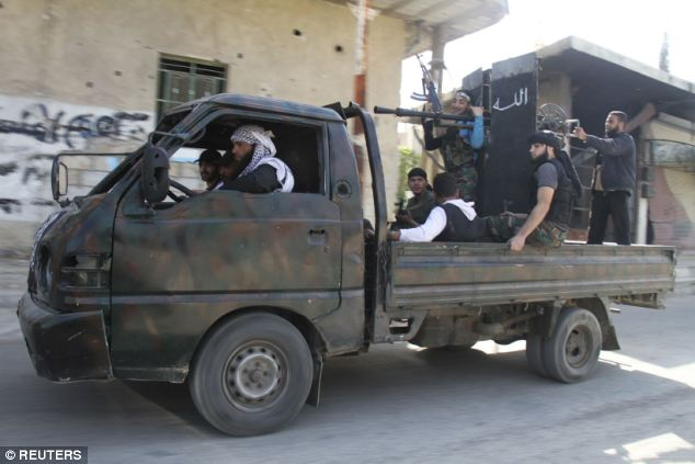 Free Syrian Army fighters, on a pick-up truck, head towards the frontline where clashes with forces loyal to Syria's President Bashar al-Assad are taking place in the al-Ziyabiya area, in Damascus