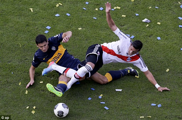 Ouch: Burdisso goes straight through in the challenge surrounded by ticker tape on the field