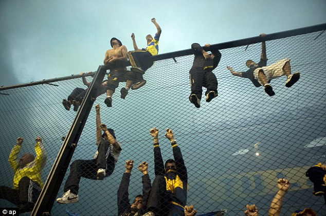 Up high: Boca fans climb up the fencing as they try to get a better view of the game