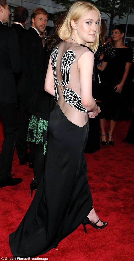 Sister act: Actresses Dakota (L) and Elle Fanning both chose striking dresses and outrageous eye make-up