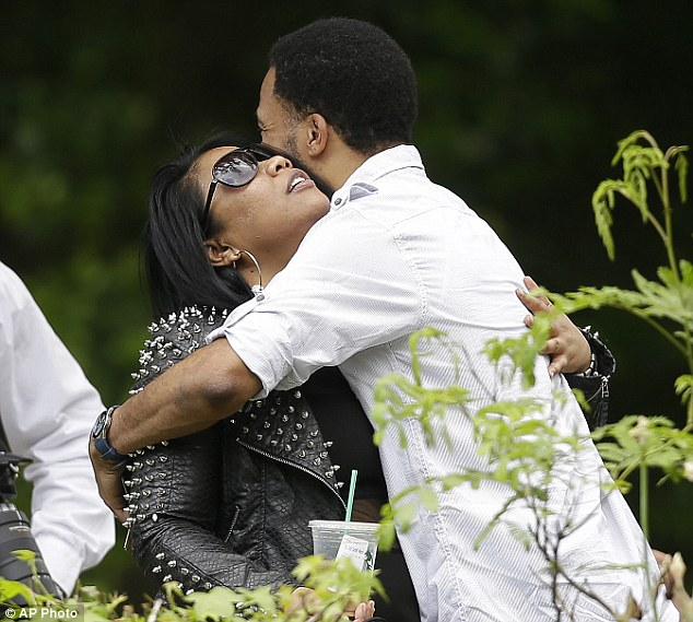 Sadness: Mourners hug outside the funeral home where Kriss Kross rapper Chris Kelly's public wake was held on Wednesday in Atlanta