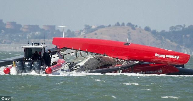 Rescue attempt: Coastguards attend to the scene of where the Artemis Racing AC72 catamaran capsized