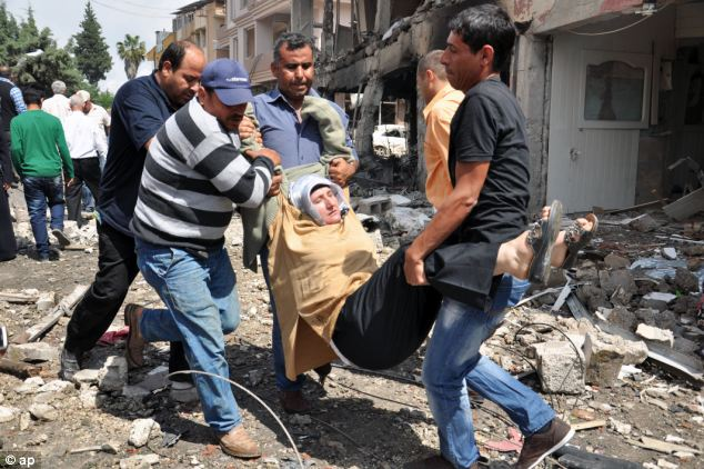 People carry a woman injured in the double blast. Suspicion immediately fell on Turkey's neighbours, Syria