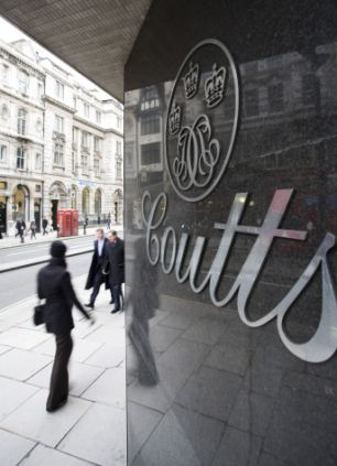 A pedestrian walks past a branch of Coutts & Co.,