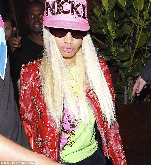 Shielded: Nicki covered up as she headed into the eatery to meet with mother Carol