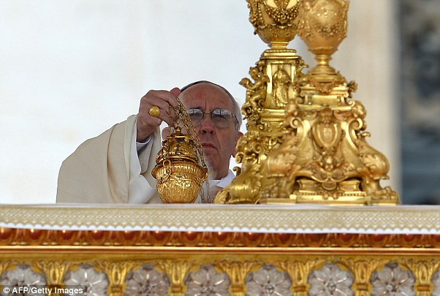 Pope Francis places a thurible at the altar in St. Peter's Basilica at the Vatican as he leads his first Canonization mass