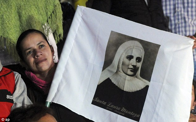 A woman holding a poster of Mother Laura Montoya who dedicated her life to working with poor people and became the country's first saint after Pope Francis canonized her in Rome today