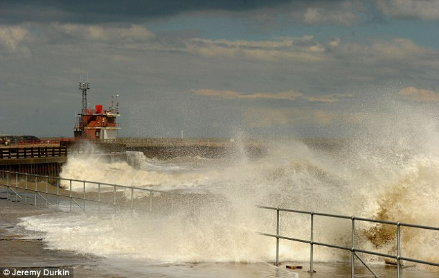 Crash: Waves smash against the shore in Great Yarmouth harbour, Norfolk, during the cold and windy weather