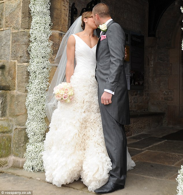 Sealed with a kiss: The newlyweds puckered up for a romantic kiss outside the church