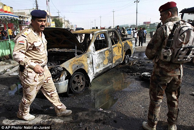 Tensions: Iraqi security forces gather at the site of the car bomb. The attacks are believed to have targeted Shiite areas as sectarian tensions heighten across the country
