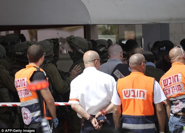 Israeli security gather outside the bank following the bungled, and ultimately tragic, heist