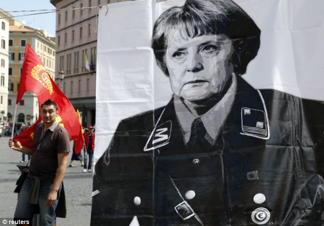 A member of Italy's metalworkers union walks by a banner with a picture of German Chancellor Angela Merkel during a demonstration in Rome. The unrest came as Mrs Merkel tried to dampen speculation over her links with East German communists