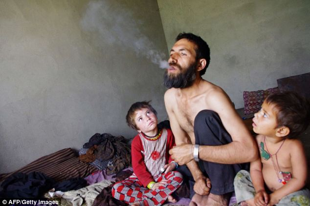 Deadly addiction: Abdul Rahman, 44, exhales after smoking opium as his children watch him at his home in Laghman province in Afghanistan. Heroin addicts in the country have tripled, according to the UN