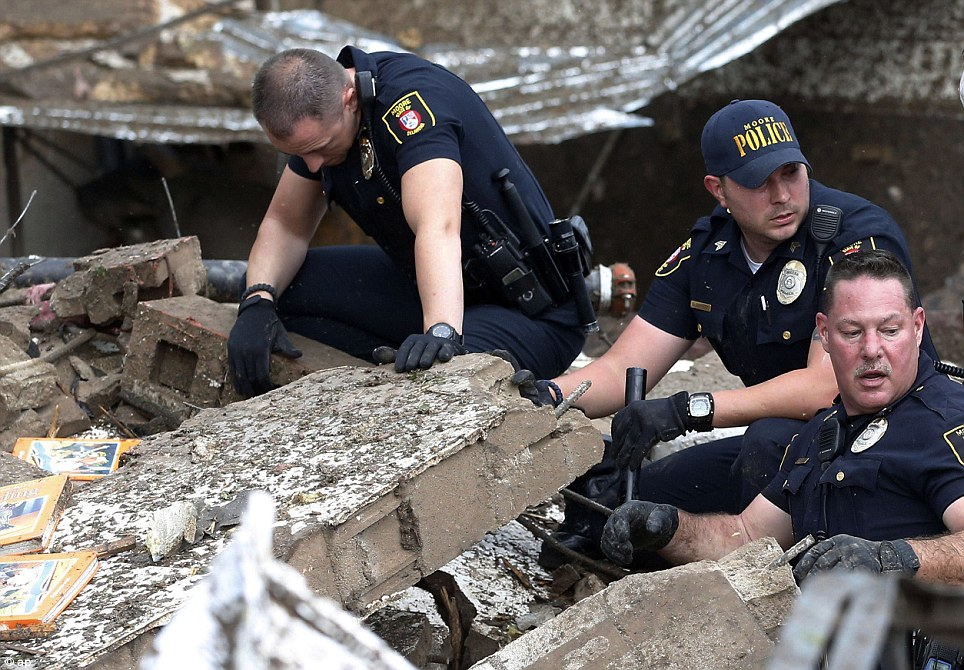 Moore police dig through the rubble of the Plaza Towers Elementary School following a tornado in Moore