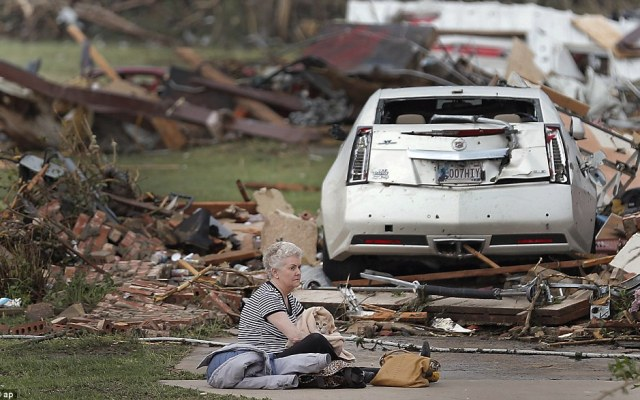 Kay James holds her cat as she sits in her driveway after her home was destroyed by the tornado that hit the area on Monday