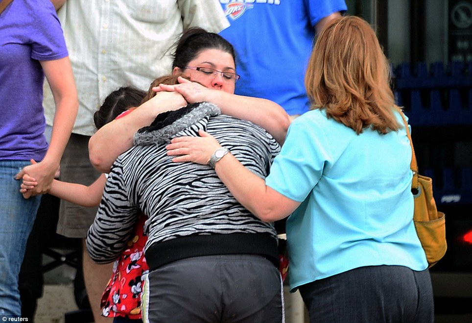 A woman is comforted after a tornado that destroyed buildings and overturned cars struck Moore