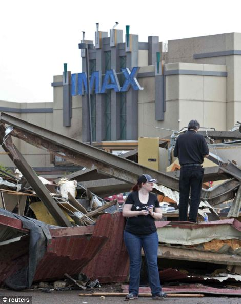 metal and debris lie in the parking lot in front of an IMAX theatre