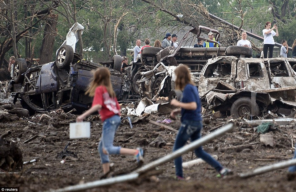 People look through the wreckage of their neighborhood after the tornado devastated the Oklahoma City suburb of Moore on Monday