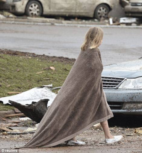 A girl walks, wrapped in a blanket, near the Moore Hospital