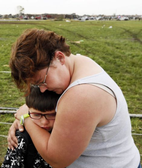 Rebekah Stuck hugs her son, Aiden Stuck, 7, after she found him in front of the destroyed Briarwood Elementary
