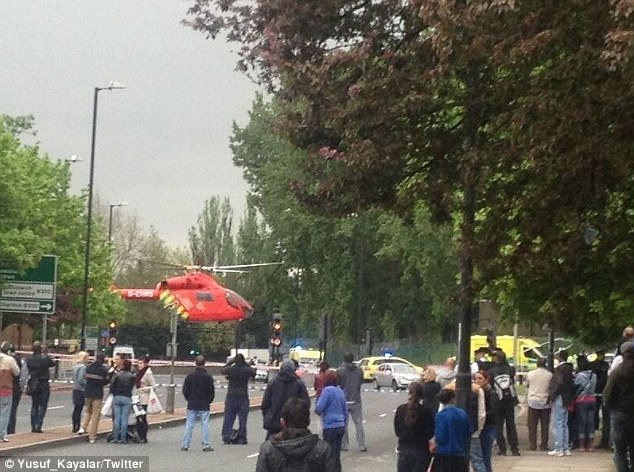 Probe: An air ambulance can be seen landing at the scene in Woolwich. Two men were later rushed to hospital while a third man died
