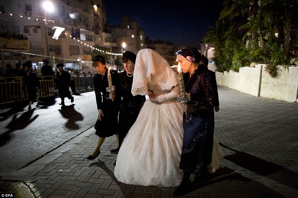 Big occasion: Ultra Orthodox Jewish bride Hannah Batya Penet is seen in a traditional white wedding dress with a veil covering her face as her female relatives escort her to the ceremony in Jerusalem, Israel