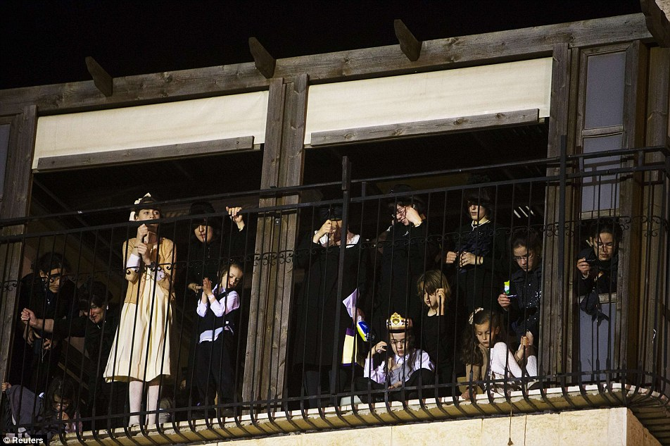 Jewish children stand on a balcony to get the best view they can of the wedding ceremony of Shalom Rokeach