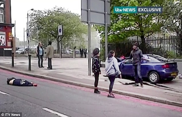 Confrontation: Two women talk to the suspected killer next to the car (right) while Ingrid Loyau-Kennett confronts the other suspected attacker (right, centre). The soldier can be seen lying dead (left)