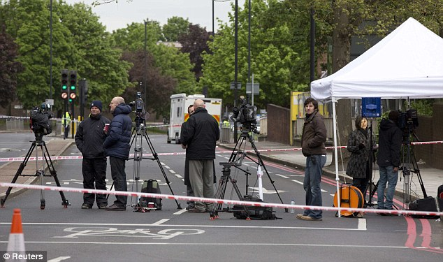 Murder scene: The media gather at the police cordon today as a forensic examination continues in Woolwich today